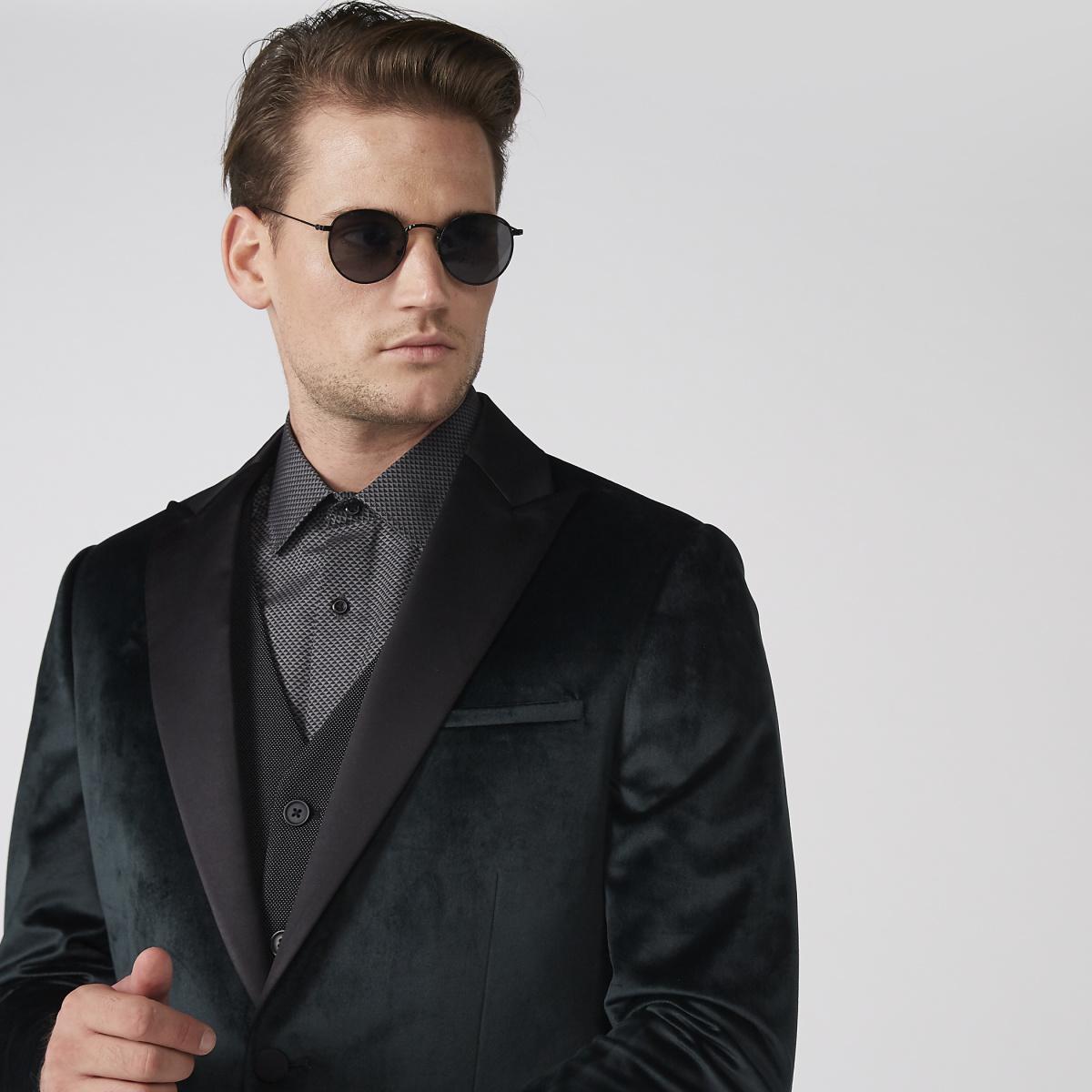Man in dark green velvet blazer with grey printed shirt